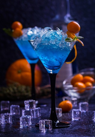 Blue cocktail in martini glasses with orange fruit and ice on black background