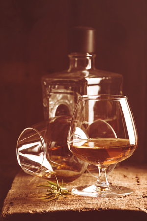 snifter: Glass of brandy or cognac and bottle on old oak wooden table. Dark photo. Stock Photo