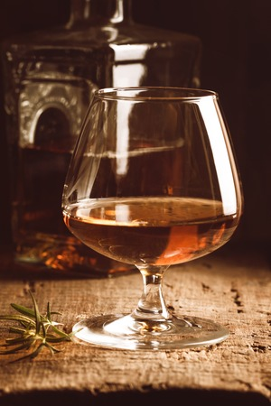 Glass of brandy or cognac and bottle on old oak wooden table. Dark photo. Stock Photo