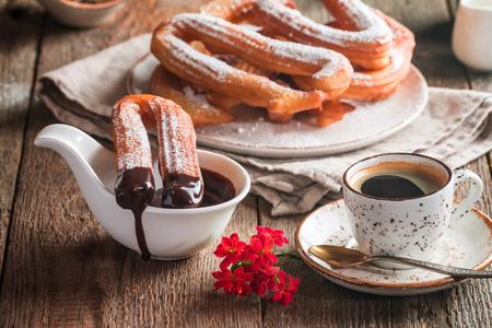 チュロス、コーヒー、ホット チョコレートを木製のテーブル