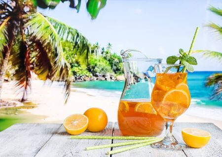 Glass of summer ice tea drink with lemon on the beach against the sea