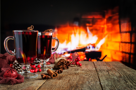 Hot mulled wine in a glass with orange slices, anise and cinnamon sticks on vintage wood table. Fireplace as background. Christmas or winter warming drink. Stock Photo