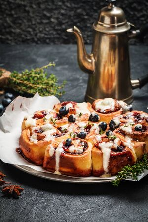 danish: Cinnamon buns with lemon, blueberry and thyme on black background