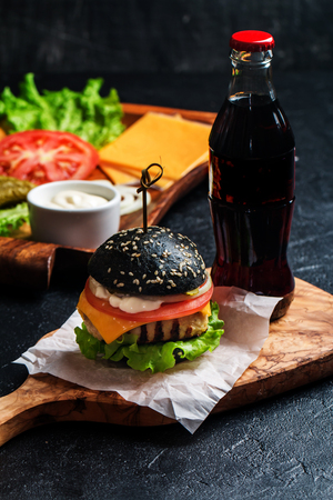 vegetable carbon: Homemade black burger with grilled chicken patty on dark background Stock Photo