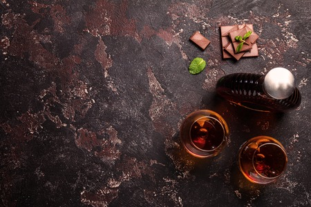 Two glasses of brandy or cognac and bottle with chocolate on dark background. top view with copy space