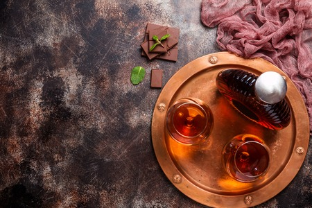 snifter: Two glasses of brandy or cognac and bottle with chocolate on dark background. top view with copy space