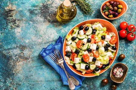 Greek salad with fresh vegetables, feta cheese and black olives on blue background, top view with copy space