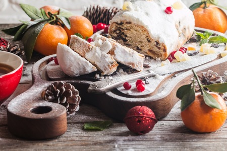 Christmas stollen, traditional German, European festive dessert cut into pieces on wooden background. Stock Photo