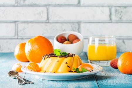 nostalgy: mango orange pudding on white plate with fruits on wooden table
