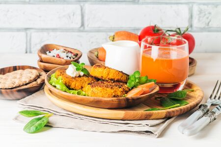 Healthy vegetarian carrots cutlets on white wooden background