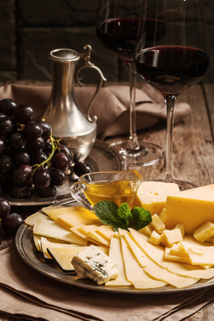 amorousness: Refined still life of red wine, grapes and cheese on metal tray on wooden table, dark background Stock Photo