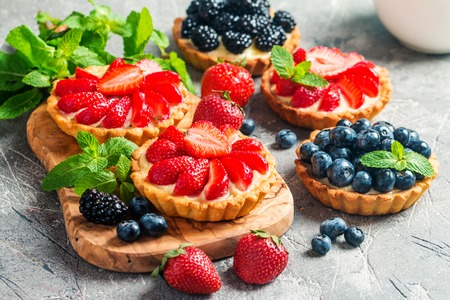 Fresh homemade berrie tarts with blueberries and strawberries on gray background Stock fotó