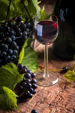 Red wine and grapes in vintage setting on wooden background