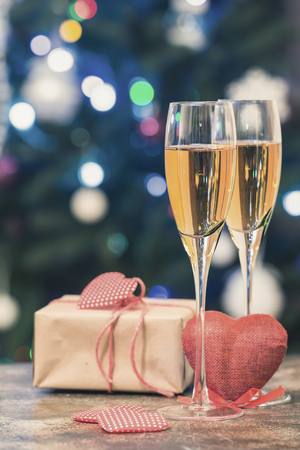 Valentines Day still life with pair of Champagne flute glasses, gift box and red heart on bokeh background Stock Photo
