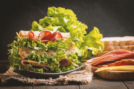 medium group of people: Club sandwich on a rustic table Stock Photo