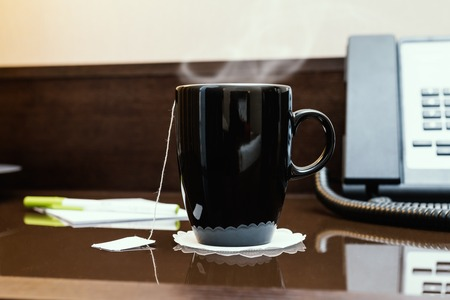 Black cup of hot tea on a glass table in a hotel room