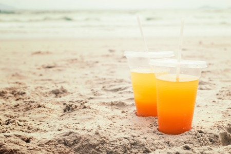 Orange juice in a glass on the beach. Summer concept.