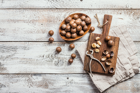 Macadamia nuts on cutting board over white wooden table, top view Stock Photo