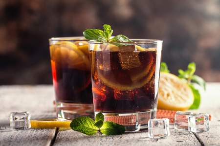longdrink: Fresh made Cuba Libre with brown rum, cola, mint and lemon on wooden background
