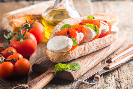Caprese sandwiches with pesto sauce and olive oil on wooden background Standard-Bild