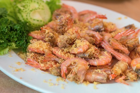 Close up shrimps cooked with garlic and dill on white plate