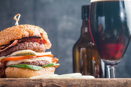 Homemade fresh hamburger and dark beer on wooden background in vintage style