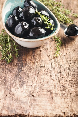 cooking oil: Bowl filled with fresh black olives Stock Photo