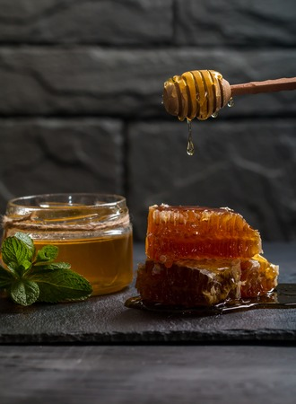 Honey dripping from a wooden dipper Stock Photo