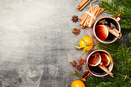 Christmas mulled wine with spices in copper cups on dark background. Top view with copy space Reklamní fotografie