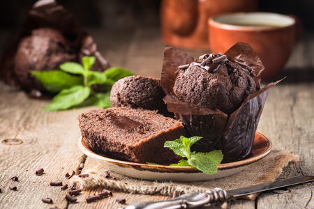 Homemade delicious chocolate muffins with mint and chocolate on wooden background close-up