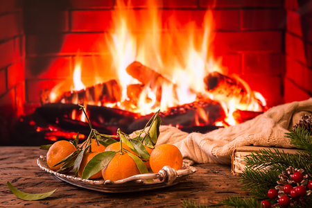Tray with tangerine, book, warm blanket and fir tree on wooden table in front of fireplace. Christmas or winter composition.