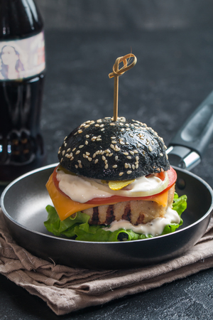 black burger with grilled chicken patty