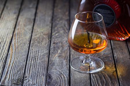 Glasse of brandy or cognac and bottle on dark background.