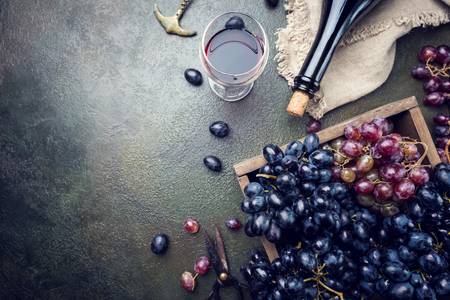 A bottle of red wine with grapes