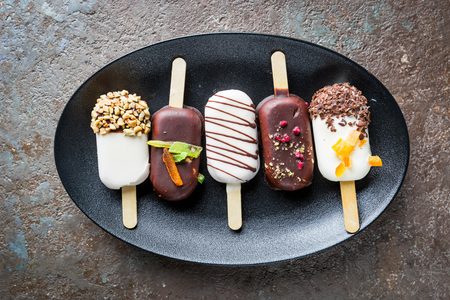 vanilla popsicles with chocolate Imagens