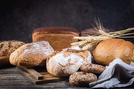 Auswahl an frisch gebackenem Brot und Brötchen auf Holztischhintergrund