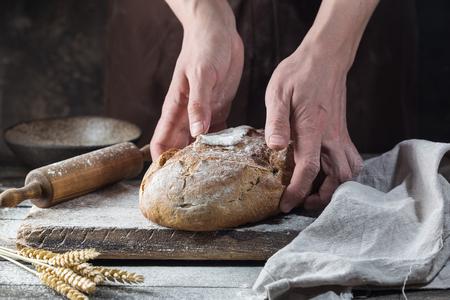 Panadero cocinando pan. El hombre echa harina sobre la masa. Manos del hombre haciendo pan