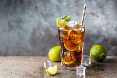 Fresh made Cuba Libre with brown rum, cola, mint and lemon on gray stone background Imagens