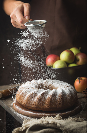 Rustic Style Apple Bundt Cake Sprinkled with Icing Sugar on old wooden table with woman hands