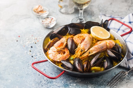 Traditional spanish seafood paella in a fry pan with white wine