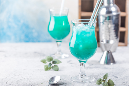 Colorful summer cocktail Blue Hawaii or iced blue lagoon alcohol drink with mint on light stone background Reklamní fotografie