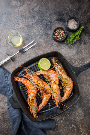 Grilled giant tiger prawns in frying pan with lemon and spices on vintage dark