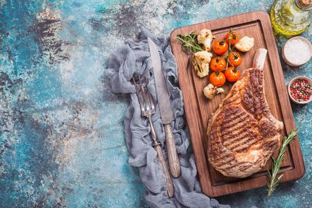 Succulent grilled tomahawk beef steak on the bone with seasonings, fresh rosemary and grilled vegetables on cutting board, top view