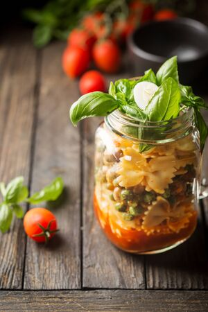 Italian Pasta with tomato sauce, mushrooms, peas and cheese in a jar. Food for work and office