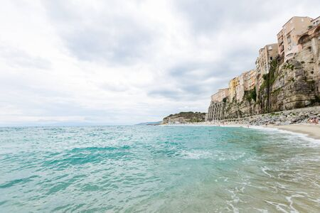 Tropea town and beach coastline of Tyrrhenian Sea with turquoise water, colorful buildings on top of high big rocks, view from Sanctuary church of Santa Maria dell Isola, Calabria, Southern Italy