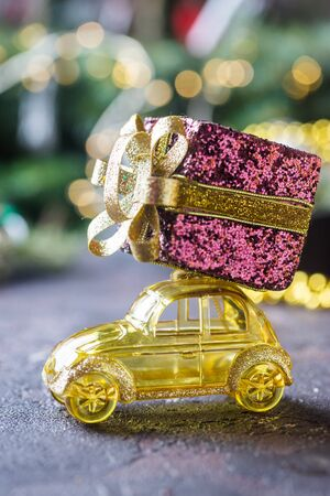 Yellow retro toy car delivering Christmas or New Year gifts on dark background