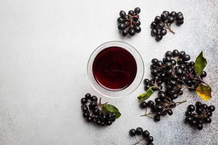 domowe wino lub likier z czarnej aronii z dojrzałymi jagodami, widok z góry