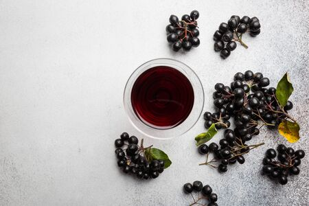 homemade black chokeberry wine or liqueur with ripe berries, top view