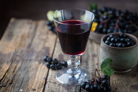 homemade black chokeberry wine or liqueur with ripe berries on wooden background