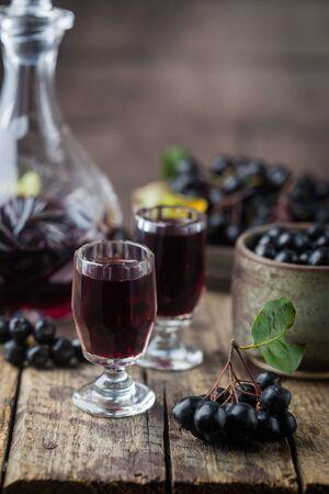domowe wino lub likier z czarnej aronii z dojrzałymi jagodami na drewnianym tle Zdjęcie Seryjne